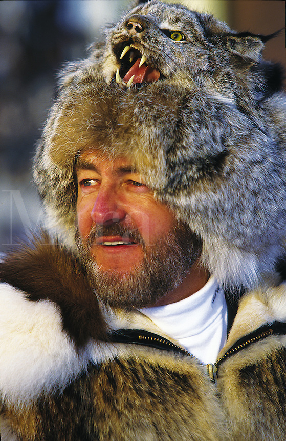 A man wears a bobcat hat and fur coat in the deep Alaskan cold. Alaska.