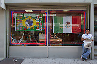 New York, NY Saturday, June 14, 2014: A man reads a newspaper while a storefront window is adored with World Cup paraphernalia in the Jackson Heights neighborhood of Queens, New York.