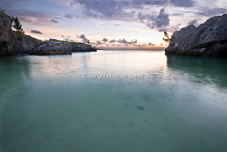 A small bay sheltered by the rocky coastline, with calm waters and a fisherman on the left side on the edge of the cliff. Bermuda