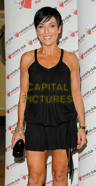 "JESSIE WALLACE .At ""The Sound Of Musicals"" tribute show, The Dorchester hotel, Park Lane, London, England, UK, .July 12th 2009..half length black dress tanned fake tan clutch bag mini smiling.CAP/CAN.©Can Nguyen/Capital Pictures"