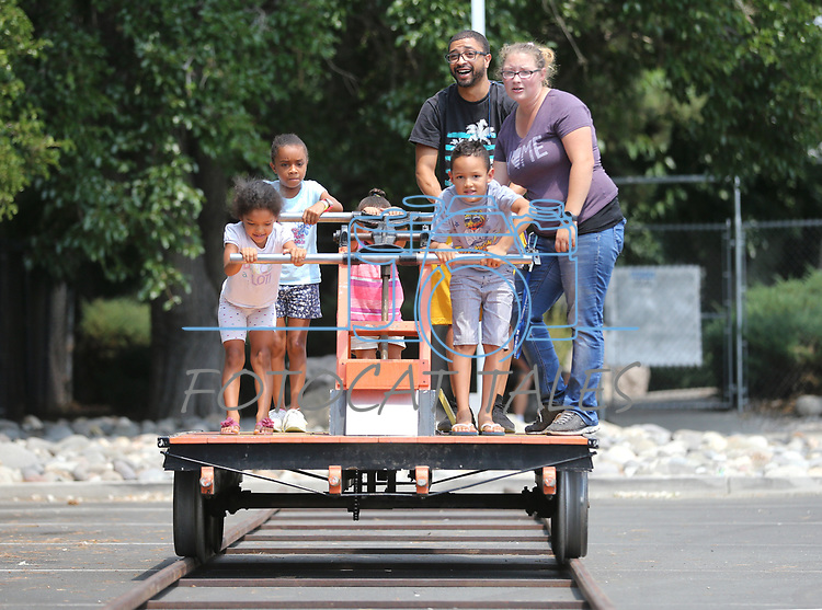 Locals ride the Nevada State Railroad Museum handcar during the Touch-a-Truck event at the Carson City Library in Carson City, Nev., on Saturday, Aug. 5, 2017. From left, are Kelly Penafiel, 5, Aaliyah Julian, 9, Tamia Julian, 3, Kevin Julian, Brian Penafiel, 7, and museum attendant Cristol Digangi. More than 600 people participated in this year&rsquo;s Summer Learning Challenge, themed &ldquo;Build a Better Community&rdquo;.<br /> Photo by Cathleen Allison/Nevada Photo Source