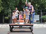 """Locals ride the Nevada State Railroad Museum handcar during the Touch-a-Truck event at the Carson City Library in Carson City, Nev., on Saturday, Aug. 5, 2017. From left, are Kelly Penafiel, 5, Aaliyah Julian, 9, Tamia Julian, 3, Kevin Julian, Brian Penafiel, 7, and museum attendant Cristol Digangi. More than 600 people participated in this year's Summer Learning Challenge, themed """"Build a Better Community"""".<br /> Photo by Cathleen Allison/Nevada Photo Source"""