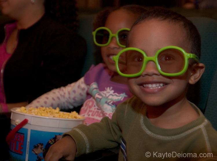 Brother and sister with a big bucket of popcorn wear 3D Chicken Little glasses to see Chicken Little at El Capitan Theatre in Hollywood, CA