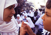 ISRAELE, Gerusalemme: primo piano di una donna con velo bianco e di un ragazzino. leloro mani si toccano. Sullo sfondo un mercato della città.