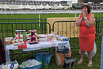 Royal Ascot horse racing Berkshire. 2016. Heath side of racecourse, a group of friends on an away day break with picnic table and food watch the racing. All the other members of the group are sitting down, while this lady organises the picnic table. This is an annual event. They have come down in a stretch limo.