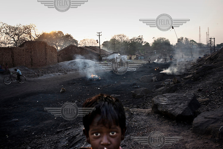 A child looks on as, beyond, fires process coal in make charcoal in Bokapahari Village. Coal fires rage just below the surface of the ground, making it too hot to walk with naked feet. Noxious gases spew up from fissures, rendering the environment toxic. Residents who live above the furnace make $2 a day collecting small chunks of coal that they sell to illegal middlemen. One or two houses collapse annually into vast underground caverns left unfilled by abandoned mining operations.