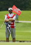 SINGAPORE - MARCH 08:  Ai Mayazato's caddie holds flag on the par tree 11th hole during the final round of HSBC Women's Champions at the Tanah Merah Country Club on March 8, 2009 in Singapore. Photo by Victor Fraile / The Power of Sport Images
