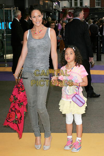 """CLAIRE MERRY & TEA HENRY.UK Premiere of """"Hannah Montana: The Movie"""" at the Odeon Leicester Square, London, England. .April 23rd 2009 .full length grey gray vest top tank daughter mother mom mum family holding hands yellow pink peep toe shoes jeans denim .CAP/AH.©Adam Houghton/Capital Pictures."""