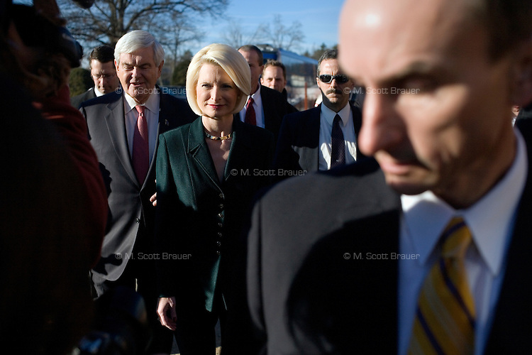 Surrounded by security, former Speaker of the House Newt Gingrich and his wife Callista arrive for a campaign event at BAE Systems, a major defense contractor, in Nashua, New Hampshire, on Jan. 9, 2012.  Gingrich is seeking the 2012 Republican presidential nomination.