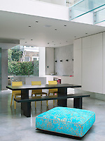 A bright blue ottoman, one of the few pieces of furniture with a pattern, in front of the steel dining set. The minimal kitchen can be seen behind
