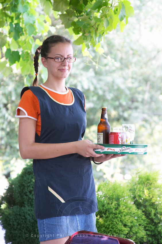 A young waitress with pig tail pigtail hair style and glasses serving a beer and a Coca Cola on a tray in a bar. Near Dupilo, Golubovic Montenegro, Balkan, Europe.