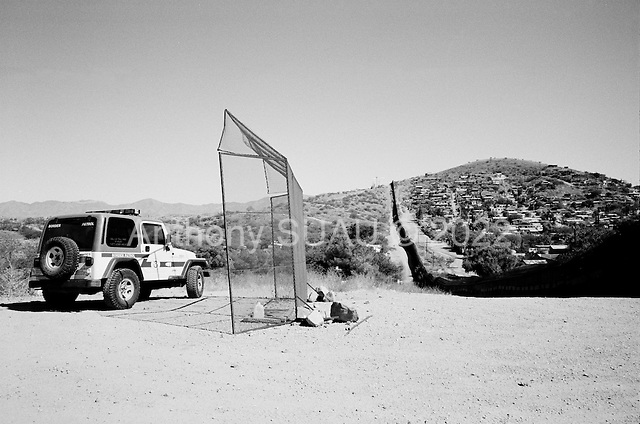 Nogales, Arizona.USA.October 20, 2006..The USA border fence and border patrol vehicle, protected by a second fence from Mexicans on the other side throwing rock at it. The port of entry into the USA, Nogales is near by. The city  is divided between Nogales Mexico and Nogales USA. The fence extends for several miles in either direction off the port of entry - then there is little to stop people from crossing illegally. Nogales is flooded with Mexicans legal and illegal and is mostly a transit and shopping town.