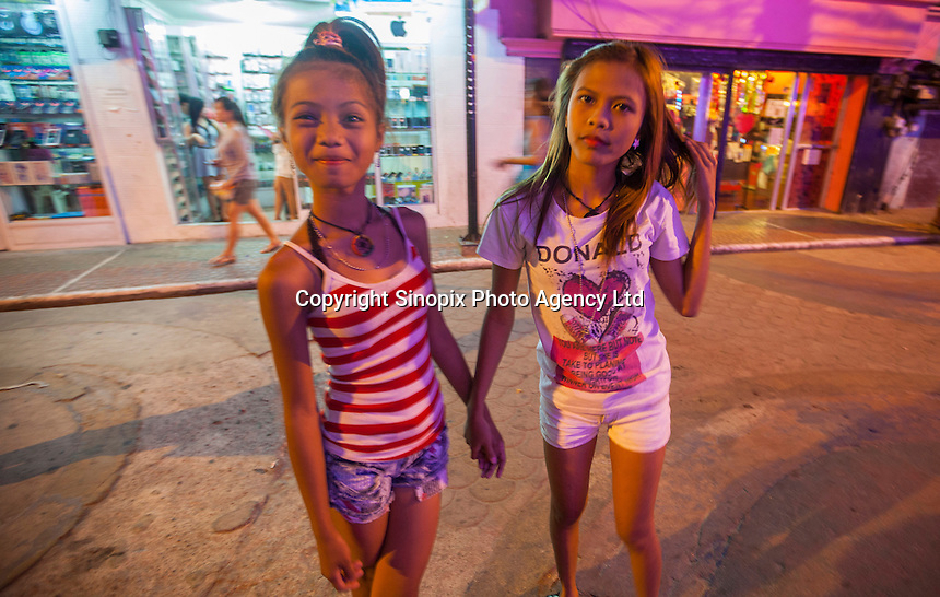 Possible underage prostitutes are seen on Fields Avenue, the main strip of bars offering cheap prostitutes that runs through Angeles City, Republic of the Philippines, 08 November 2014. The 'sin city', which sprung up on the fringes of a US Air Force base during the Vietnam war, has a reputation for cheap sex, and was a favourite destination for alleged murderer Rurik Jutting, who used to fly to Angeles City from Hong Kong for debauched weekends. The British banker is currently on remand at a secure facility in Hong Kong for allegedly murdering two Indonesian prostitutes in his flat whilst high on alcohol and cocaine.