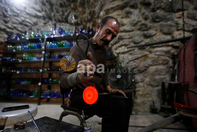 Palestinian Yacoub al-Natsheh, professional glassblower who has been forming glass for over 40 years, works at his workshop near the Ibrahimi Mosque, in the West Bank city of Hebron. A glassblower or designer is responsible for designing, producing, decorating and finishing pieces of glass including, architectural glass, exhibition pieces, giftware, mirrors, stained, glass, windows and tableware. Photo by Wisam Hashlamoun