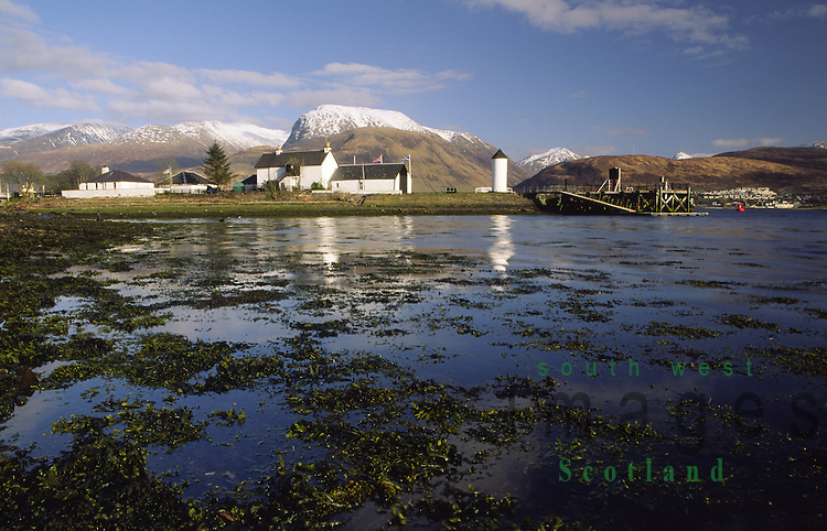 Corpach on the edge of Loch Eil looking across to lighthouse at the start of the Caledonian Canal with Fort William and a snow topped Ben Nevis behind Lochaber in the Scottish Highlands Scotland UK