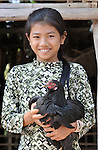 Sum Thida, 12, cares for chickens at her family's home in Soepreng, a village in the Kampot region of Cambodia.