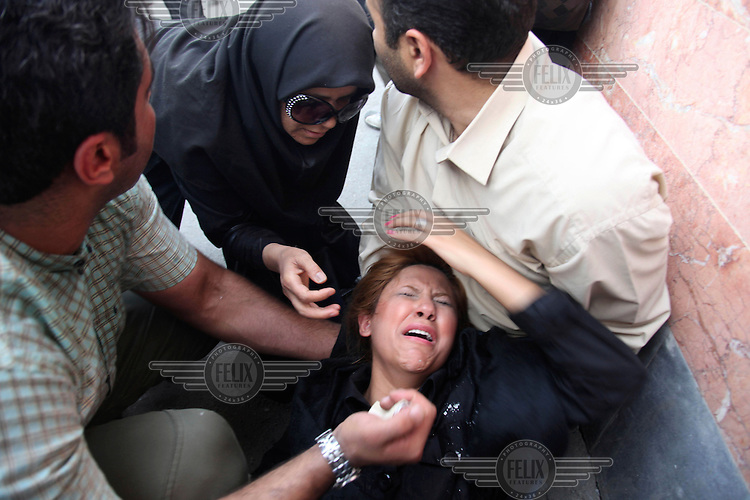 A woman injured after police fired tear gas on Khosh Street. Following a disputed election result, thousands of supporters of opposition candidate Mir-Hossein Mousavi took to the streets in protest.
