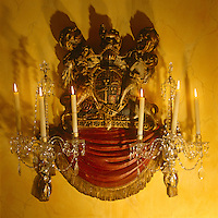 In the library a candle sconce incorporating the Royal Arms of the Stuarts shimmers with crystal drops