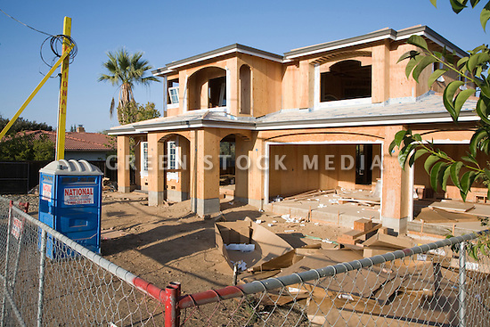 A large two-story wood frame house construction site in Cupertino, California, in Silicon Valley of the San Francisco Bay Area. Large amounts of wood and other raw materials are being used to build this new house on a lot where a single-story home was demolished.