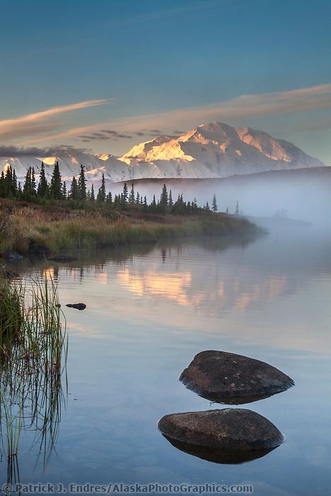 Rocks along the shore of Wonder lake as morning fog rises over the calm water at sunrise, Denali looms in the distance, Denali National park, Alaska.
