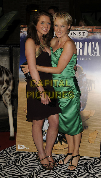 """HELEN FLANAGAN & SALLY WHITTAKER .Coronation Street """"Out Of Africa"""" DVD Premiere at Odeon Printworkds Centre, Withy Grove, Manchester, England. .November 4th 2008.full length purple aubergine dress gold trim black clutch bag green silk satin hug embrace .CAP/CAN.©Can Nguyen/Capital Pictures."""