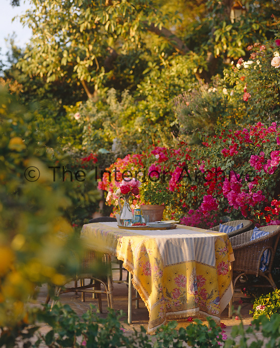 A colourful length of fabric covers the table in this sunlit corner of the garden bright with pink bougainvillea