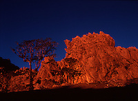 "August 9th, 2004-Mt. Matebian, Timor-Leste -The rocky face near the summit of Mount Matebean ""Mountain of the Dead"" in Baucau District is aflame in the golden light of the setting sun. Mt. Matebian towers to the height of 7,782 feet and is the 2nd highest mountain in Timor-Leste..Photograph by Daniel J. Groshong/Tayo Photo Group"