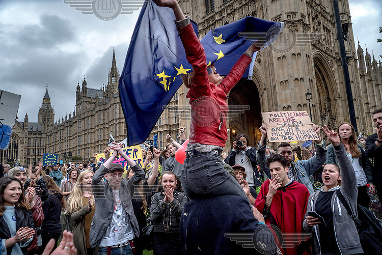 A woman waves an EU flag during a rally in Parliament Square attended by tens of thousands of people protesting the outcome of the EU referendum and declaring their support for the EU.