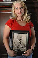 Becky Martin poses with a picture of her husband who lost his life while on his third rotation to Iraq.