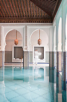 The indoor ozone-heated pool is framed by Moroccan arches and blue mosaic tiles