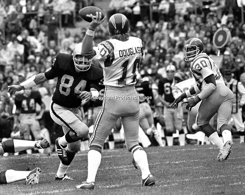 Oakland Raiders Tony Cline puts a rush on San Diego quarter back Bobby Douglas...(1975 photo/Ron Riesterer)
