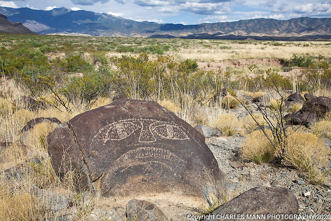 A petroglyph resembling an eerie face stares skyward with the rugged Sacramento Mountains in the backdrop at Three Rivers State Park near Tularosa in sourthern New Mexico