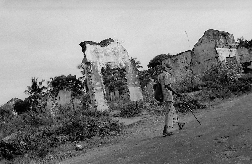 An elderly Tamil man walks through a neighborhood heavily damaged by shelling a decade ago during the ongoing conflict between the Tamil Tigers and the Sri Lankan government in Jaffna, Sri Lanka, Saturday, Apr. 24, 2004.