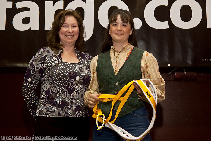 Jessie Royer recieves the Golden Harness award for her lead dog Kuling from the Nome Mayor Denise Michaels at the Nome awards banquet during Iditarod 2009