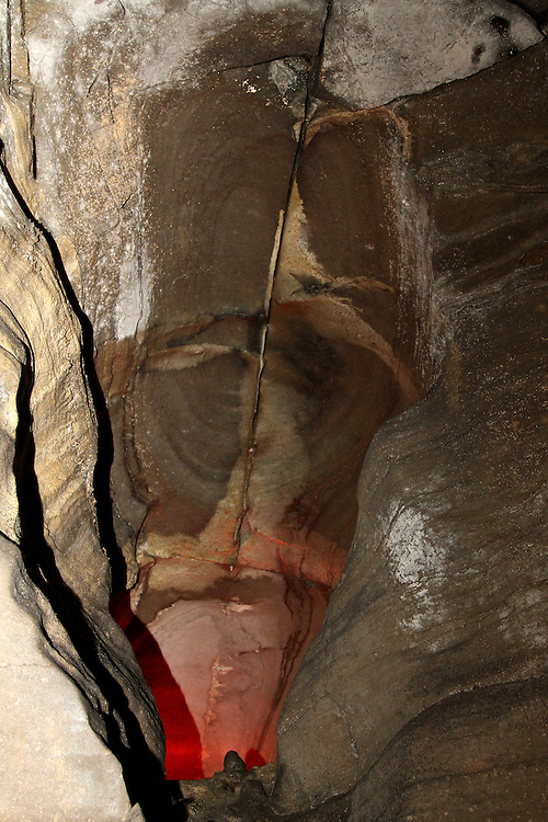The glow of a red light adds to the shadows and fissures in a portion of the cave wall in Howe Caverns.