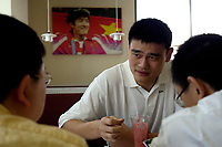NBA Houston Rockets player Yao Ming Yao Ming discusses with his agents before a press conference for the 2007 Special Olympics in Beijing, China July 21, 2006.  The photo on the wall is Chinese hurdle champion Liu Xiang.  (photo by Lou Linwei/Sinopix)