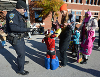 NWA Democrat-Gazette/ANDY SHUPE<br /> Kelly Howell (right) reacts Thursday, Oct. 31, 2019, as her son, Junior Howell, 3, greets Jason Carroll of the Fayetteville Police Department as Carroll hands out police badge stickers during the 18th Annual Trick-or-Treat on the Square hosted by Experience Fayetteville on the Fayetteville square. Businesses on the square join city departments in handing out candy to trick-or-treaters. Visit nwadg.com/photos to see more photographs from the evening.