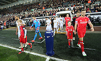 SWANSEA, WALES - MARCH 16: Team captains Ashley Williams of Swansea (L) and Jordan Henderson of Liverpool (R) lead their teams out prior to the Premier League match between Swansea City and Liverpool at the Liberty Stadium on March 16, 2015 in Swansea, Wales