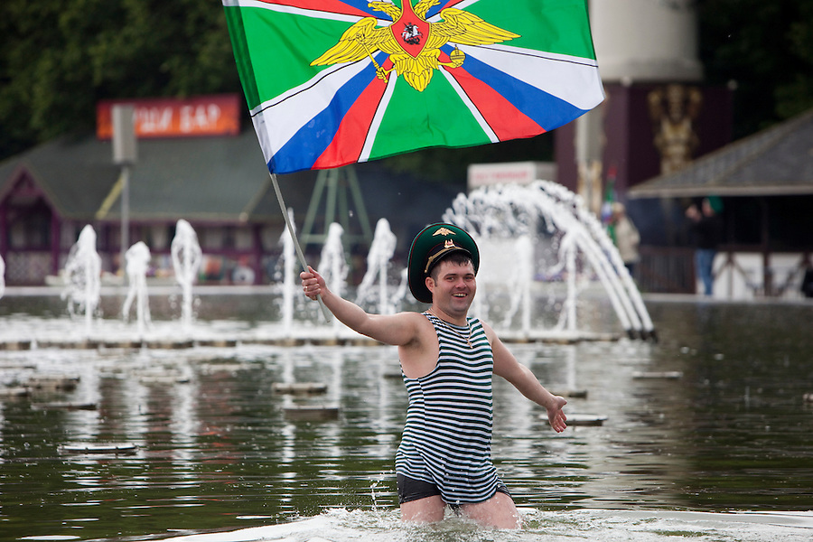 Moscow, Russia, 28/05/2010..A member of the Russian Border Troops in a Gorky park lake waves the regimental flag as the regiment celebrated their annual holiday.