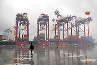 A dock worker standing in the loading area of the just completed Yangshan Deep Water Port in Shanghai, China. The port will give the city it's first deep water port, adding capacity to its formidable shipping infrastructure,  already Shanghai is expected to become world's largest freight port at the end of this year surpassing Singapore, according to materials provided by the Ministry of Commerce..
