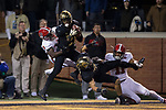 Essang Bassey (21) of the Wake Forest Demon Deacons is tackled by Kelvin Harmon (3) of the North Carolina State Wolfpack intercepting a pass intended for Jakobi Meyers (11) late in the fourth quarter at BB&T Field on November 18, 2017 in Winston-Salem, North Carolina.  The Demon Deacons defeated the Wolfpack 30-24.  (Brian Westerholt/Sports On Film)