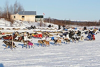 Sebastian Schnuelle runs past teams after checking in and out of the ghost-town checkpoint of  Iditarod during the 2011 Iditarod race..