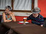 A couple has dessert and a beer at a street cafe, The colorful village of Burano, Italy.