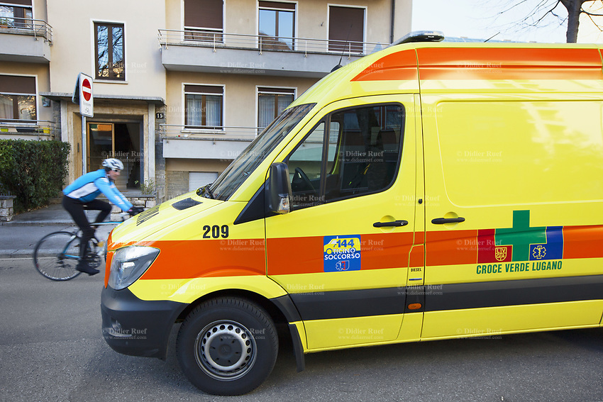 Switzerland. Canton Ticino. Lugano. Day scene for a medical emergency intervention. The paramedics team is at work in one of building's flat. The ambulance from the Croce Verde Lugano is parked on the street. A sticker with the emergency phone number (144) to reach Ticino Soccorso. TheCroce Verde Lugano is a private organization which ensure health safety by addressing different emergencies services and rescue services. A cyclist rides his bicycle on the road. 13.01.2018 © 2018 Didier Ruef