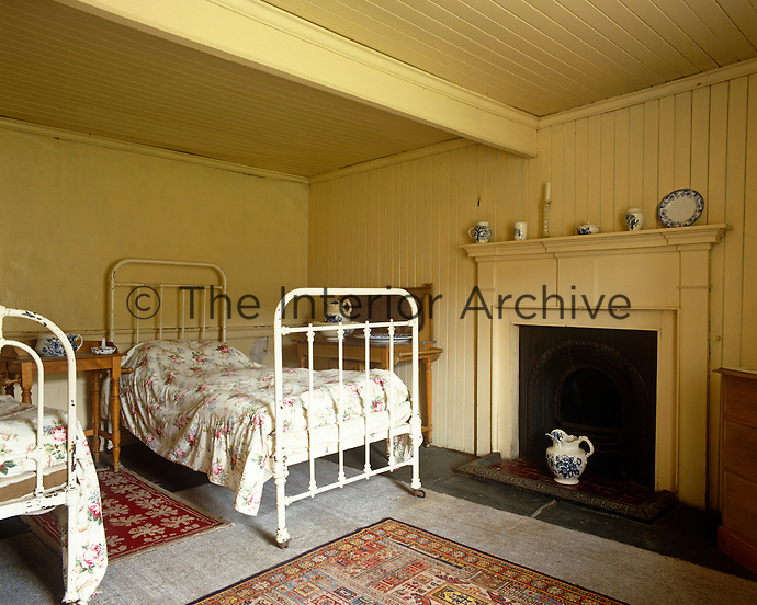 A bedroom at the fishing lodge is simply furnished with a pair of wrought-iron bedsteads
