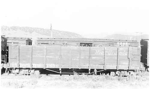Side view of D&amp;RGW high-side gondola #1830 at Peake, CO on the RGS.  The upper portion of D&amp;RGW stock car #5595 is visible behind the gon.<br /> D&amp;RGW on the RGS  Peake, CO  Taken by Ahrnke, Russell - 1951