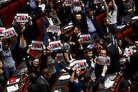 """I deputati del Movimento 5 Stelle espongono cartelli raffiguranti Silvio Berlusconi e Matteo Renzi, al termine della votazione che ha approvato la riforma della legge elettorale, alla Camera dei Deputati, Roma, 12 marzo 2014.<br /> Five Stars Movement's lawmakers hold signs portraying Silvio Berlusconi and Matteo Renzi and reading """"Deep tuning. Condamned to love"""" to protest against the approvation of the new electoral law, at the Lower Chamber in Rome, 12 March 2014.<br /> UPDATE IMAGES PRESS/Riccardo De Luca"""
