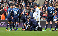 Pictured: Michu of Swansea (in white) is making sure  Scott Parker of Tottenham is alright who is receiving first aid on the ground. Saturday 30 March 2013<br />