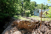 NWA Democrat-Gazette/DAVID GOTTSCHALK  The bottom of a fence post Thursday, May 25, 2017, is visible near the home of Elfi Davis caused by the series of recent rains flooding the near by creek and eroding the bank and flooding her property. The flooding has caused damage and deposited debris on her property.