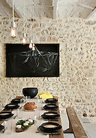 The artwork hanging on an adjacent wall and the simple crockery on the table create stunning accents of black against the neutral tones of the natural stone in the dining room walls